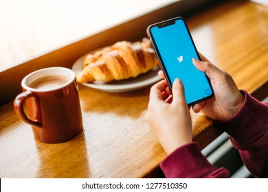 SEOUL, SOUTH KOREA - OCTOBER 15, 2018: Woman holding a iPhone X or iPhone 10 with social Internet service Twitter on screen with morning breakfast. iPhone X was created and developed by the Apple inc.