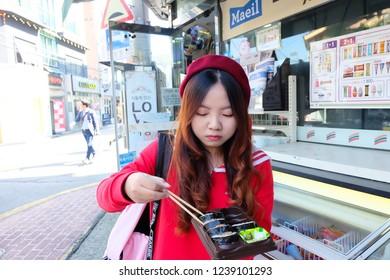 Seoul, South Korea - OCTOBER 20, 2018 : Young asian woman traveler eating food at hongdae street.