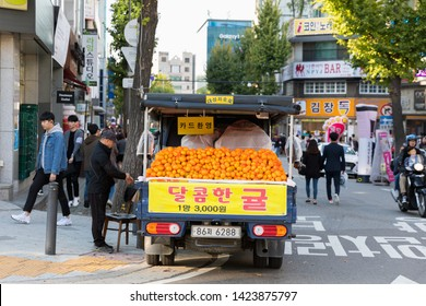 SEOUL, SOUTH KOREA - OCTOBER 21, 2018:Fresh oranges stall pick up in the car for selling at Hongdae(Hongik University) shopping street. Hongdae is a shopping cultural street for young people in Seoul.