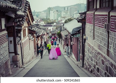 SEOUL - SOUTH KOREA - OCTOBER 21, 2016 : A couple women wander through the traditional style houses of Bukchon Hanok Village in Seoul, South Korea.