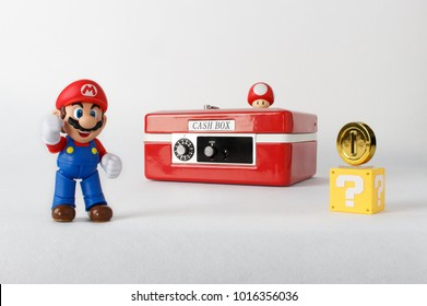 Seoul, South Korea - October 25, 2016: Super Mario figures are standing in front of a red cash box.