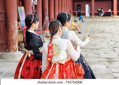 Seoul, South Korea - October 9, 2017: Pretty girls wearing Korean traditional dress Hanbok and using smartphone in Gyeongbokgung Palace. Girls taking pictures.