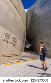 SEOUL / SOUTH KOREA-August 2018: a stylish backpacker boy standing in from of Dongdaemun Design Plaza (DDP) or Dongdaemun history & culture park.