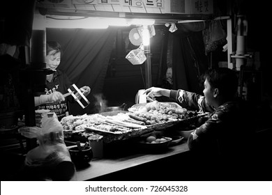 SEOUL, SOUTH KOREA-SEPTEMBER 22: A tourist chooses a barbecue while the vendor smiles in satisfaction in one street food stall on September 22, 2016 in Seoul, South Korea. Photo in black and white.