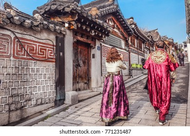 Seoul,28 November,2017.Back of two person wearing Hanbok is korea national dress walking through Bukchon Hanok Village Traditional Korean style architecture house at Historic district, Seoul,Korea