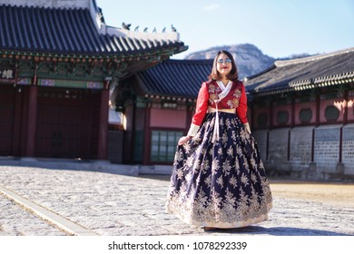 Seoul,South Korea - DEC 01 - 2016 : The beautiful woman traveller posture in Hanbok traditional Korean clothes in autumn winter at the Gyeongbokgung Palace.