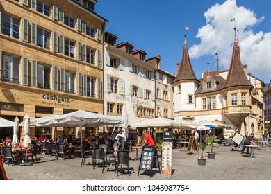 SEP 05, 2018 Neuchatel, Switzerland - Tourists enjoy outdoor dinning at Market place des Halles in front of La Maison des Halles building in Medieval ancient town of Neuchatel