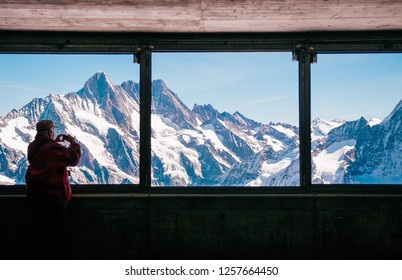 SEP 24, 2013 Jungfrau, Switzerland - Tourist enjoy Eiger and Monch peaks panoramic view through observation window of Eiger tunnel inside Swiss alps