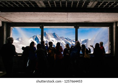 SEP 24, 2013 Jungfrau, Switzerland - Tourists enjoy Eiger and Monch peaks panoramic view through observation window of Eiger tunnel inside Swiss alps
