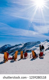 SEP 24, 2013 Jungfraujoch, Switzerland - Tourists sit on wooden chair in winter snow landscape on Jungfraujoch, top of Europe Swiss alps scenery.