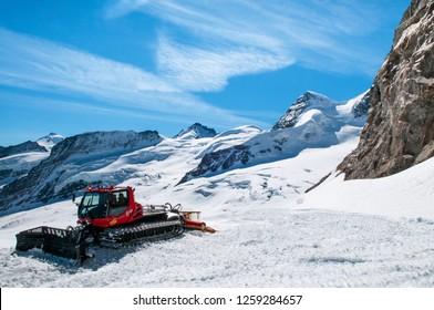 SEP 24, 2013 Jungfraujoch, Switzerland - Snowcat machine to work on a snow field winter landscape of Jungfraujoch, top of Europe Swiss alps scenery.