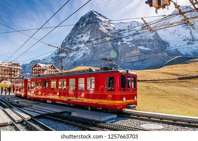 SEP 24,2013 Lauterbrunnen, Switzerland - Red Jungfrau railway train at Kleine Scheidegg station for Jungfraujoch  with Swiss alps mountain Eiger and Monch peaks