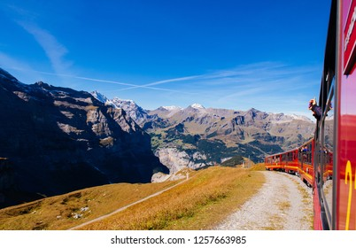 SEP 24,2013 Lauterbrunnen, Switzerland - Red Jungfrau railway train from Kleine Scheidegg station climbing to Jungfraujoch pass grassfield and Swiss alps mountain range