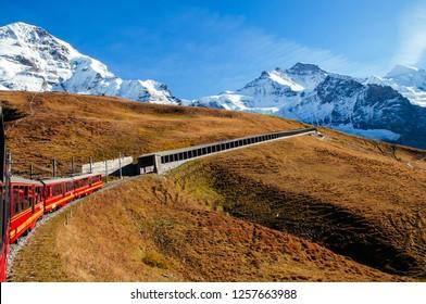 SEP 24,2013 Lauterbrunnen, Switzerland - Red Jungfrau railway train at Kleine Scheidegg station climbing to Jungfraujoch pass grassfield and Eiger, Monch mountain peaks
