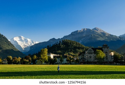 SEP 25, 2013 Interlaken, Switzerland - Peolpe in green field Hohematte park and Swiss alps snow peak Jungfrau of Interlaken, famous town for tourists