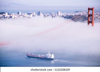 SEP 26, 2009 San Francisco, USA - San Francisco Golden Gate bridge on foggy day dramatic evening light cruise ship pass under view from Marin Headland side