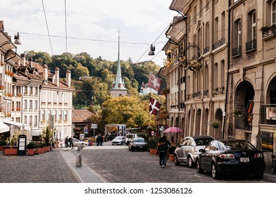 SEP 27, 2103 Bern, Switzerland - People walking on street among vintage historic Swiss style residential buildinfgs with Nydeggkirche Protestant church bell tower in old town Bern
