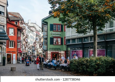 SEP 28,2013 Zurich, Switzerland - Beautiful colourful old vintage buildings and street cafe with tourists sitting outside in Zurich Old town Altstadt area