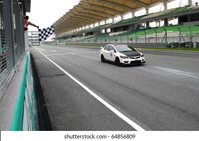 SEPANG - CIRCA MAY 2010: Checker flags finishing flag as white color HONDA car cross the finishing line at Sepang circuit Malaysia, during the HPC track day circa May 2010.