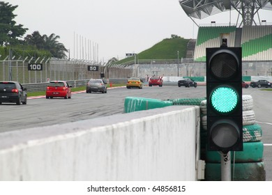 SEPANG - CIRCA MAY 2010: Green traffic light and race cars approach a sharp corner during HPC track day circa May 2010 at Sepang circuit Malaysia.