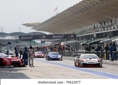 SEPANG - JUNE 19: Cars exit the pitlane after tire change and refuel at the Sepang International Circuit during the qualifying rounds of the Japan SUPER GT Round 3 on June 19, 2011 in Sepang, Malaysia