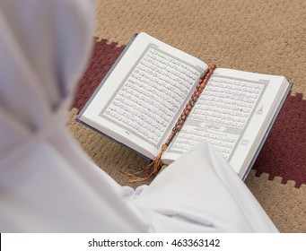 SEPANG, MALAYSIA - 4 AUG 2016: Backview of a muslim woman reciting al Quran in mosque. (Focus is on the al Quran).