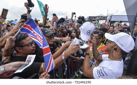 SEPANG, MALAYSIA : OCTOBER 01, 2017 : Lewis Hamilton of Great Britain and Mercedes signs autographs for fans before the Malaysia Formula One (F1) Grand Prix at Sepang International Circuit.