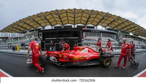 SEPANG, MALAYSIA - SEPTEMBER 28, 2017 : Team members push Scuderia Ferrari driver, Kimi Raikkonen car to the garage ahead of the Malaysia Formula One (F1) Grand Prix at Sepang International Circuit.