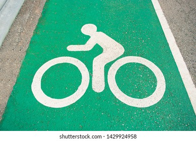 Separate bicycle lane for riding bicycles.Bicycle icon on the lane .New public asphalt bicycle lane  close up beside the road.White painted bike on asphalt.