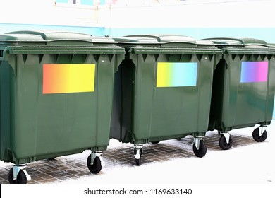 Separate waste collection. Green garbage cans without labels with colored stickers