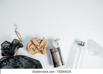 Separate waste with Plastic Bottle Tin Bank and Paper On White  Background, Top View