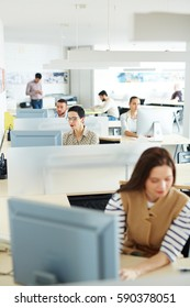 Separate workplace cubicles with different people sitting at them in open space of modern office