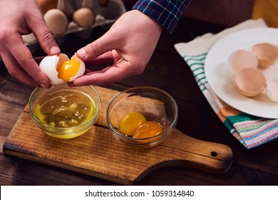 Separated eggs over dark brown wooden table. Man separating the yolk from the egg white.