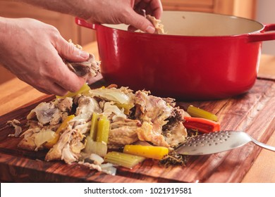 Separating the meat from the bones after boiling leftover roasted chicken carcasses.  Meat is then placed back into soup pot.