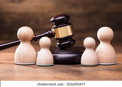 Separation Of Pawn Wooden Figure With Gavel On Wooden Table In Courtroom