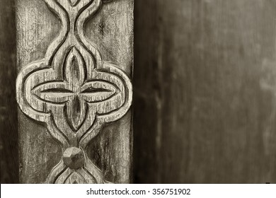 Sepia detail of a carved post in a traditional Arabian door.