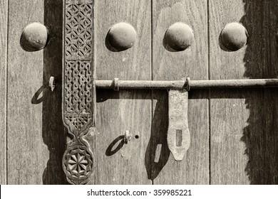 Sepia detail of a carving, doornails and lock on a traditional wooden Arabian door.