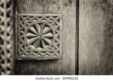 Sepia detail of a carving on a traditional wooden Arabian door.