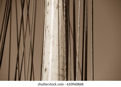 Sepia filtered image Close up Mast of historic wooden sailing ship, with rigging and ropes, blue sky and copy space.