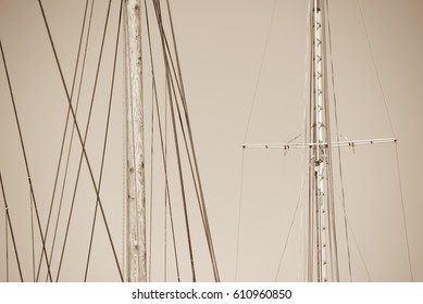 Sepia filtered image Mast of historic wooden and modern sailing ships, with rigging and ropes, blue sky and copy space.