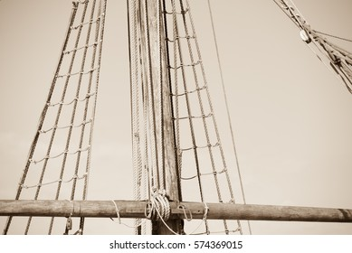 Sepia filtered image  of mast of old antique historic wooden sailing ship, with rigging and ropes, sky and copy space.