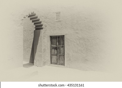 A sepia image of sunlight casting shadows from an elaborate arch near a traditional carved arabian door in the wall of a fort in Riffa, Bahrain.