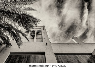 A sepia monochrome filtered view looking upwards through the leaves of a palm tree towards a windcatcher, a traditional Arabian ventilation tower on a restored adobe building in the Arabian Gulf.