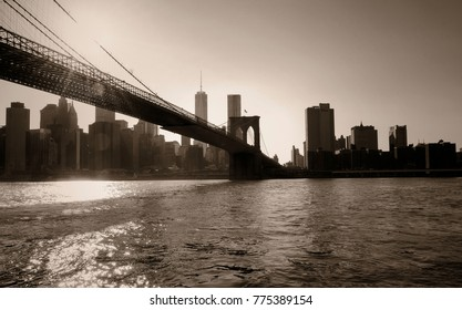 A sepia photo from Brooklyn Bridge Park at dusk. In the foreground is the river as the bridge veers into the skyline of Manhattan.