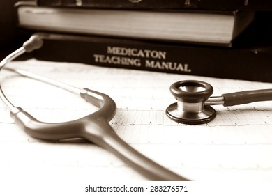 Sepia picture of stethoscope and EKG graph and medical textbooks.