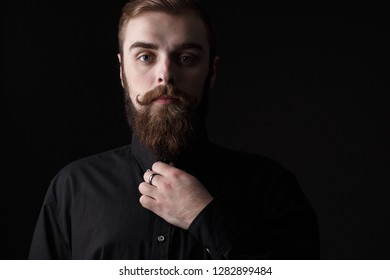 Sepia portrait of a stylish man with a beard and stylish hairdo dressed in the black shirt on the black background