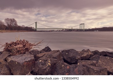 Sepia - Purple colors - Panorama on the Rhine with rocks in the foreground and view over the Rhine to the Rodenkirchen bridge. There are strong winds over the city.