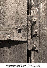 Sepia rusty old iron hinge on timber garden shed door