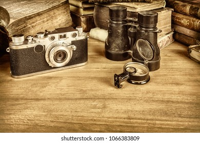 Sepia styled image of a wooden table with old books, camera, binocular and compass