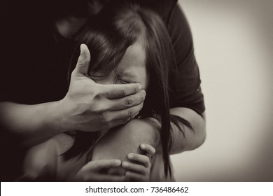 Sepia tone noice effect child abuse concept. Hand of unknown man covering scared Asian child face.